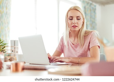 Beautiful young woman sitting at the desk in home office and working on laptop.