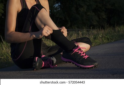 Beautiful young woman sitting down, taking a break from running in park for pulling up socks on summer evening