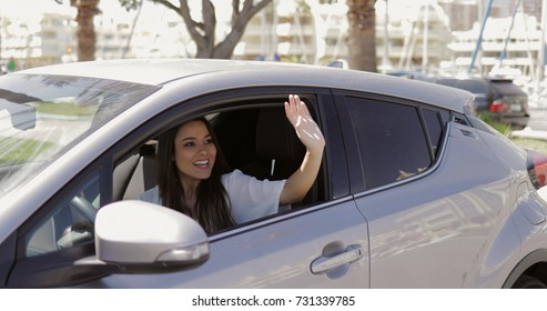 Beautiful young woman sitting inside of modern car and waving with hand greeting someone in sunny day at street.