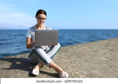 Beautiful young woman sitting with a laptop by the sea.  Webinar online teaching concept. Online work.