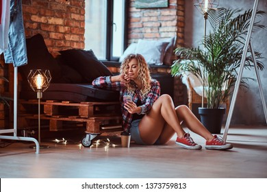 Beautiful young woman is sitting next to the pallet sofa. She is holding mobile phone. Woman wear hotpants and checkered shirt. Modern loft with brick wall at background.