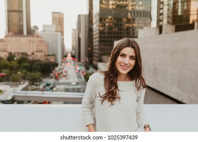 Beautiful young woman sitting on a bridge across the boulevard in urban scenery, downtown, at sunset, smiling at camera.