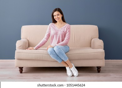 Beautiful young woman sitting on sofa, indoors