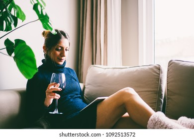 Beautiful young woman sitting on sofa, looking at tablet screen and drinks red wine (toned image, selective focus)