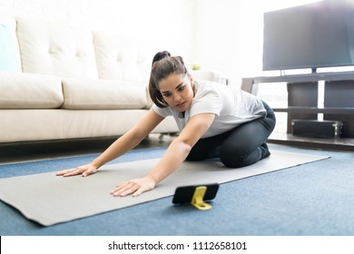 Beautiful young woman sitting on exercise mat at home learning yoga positions from online videos over her mobile phone