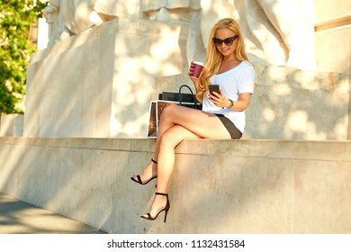 A beautiful young woman sitting on the patten of a statue wearing high heels while using her smartphone and having a coffee in the sunset
