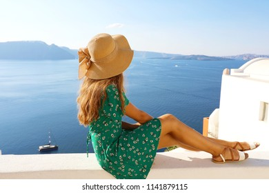 Beautiful young woman sitting on wall looking at stunning view of Mediterranean sea and Caldera in Santorini, Greece, Europe. Lifestyle woman with straw hat wearing green dress enjoy landscape view.