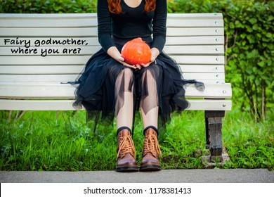 Beautiful young woman sitting on white bench with bright orange pumpkin on hands,  waiting for fairy godmother like Cinderella, brown boots, black skirt