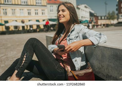 Beautiful young woman sitting on the street in city center with legs crossed on sunny day and holding mobile phone and smiling.
