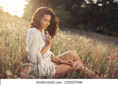 Beautiful Young Woman sitting on the field around wild flowers outdoors. Enjoy Nature. Healthy perfect smiling girl on summer lawn. Allergy free concept. Gorgeous slim mixed race Caucasian Asian model