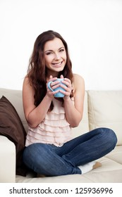 Beautiful young woman sitting on couch holding coffee cup