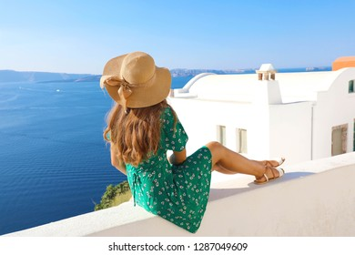 Beautiful young woman sitting on wall looking at stunning view of Mediterranean sea and Santorini village, Greece, Europe. Lifestyle woman with straw hat wearing green dress enjoy landscape view.