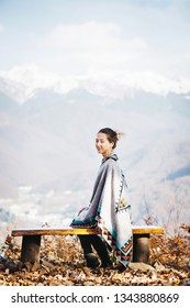 Beautiful young woman sitting on bench in front of snowy mountain ridge, looking at camera.