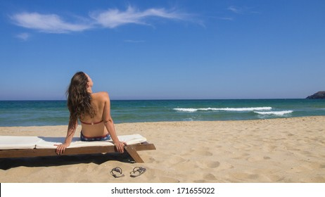 Beautiful young woman sitting  on a lounge and enjoying the view at the beach on a beautiful sunny day.