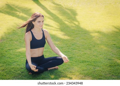 Beautiful young woman is sitting on a green lawn in meditation pose, doing yoga.