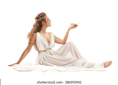 The Beautiful Young Woman Sitting on the Floor, Holding the Gold Bowl with Nectar and Wearing White and Gold Greek Costume on the White Background