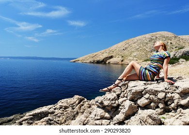 Beautiful young woman sitting on rock and looking at sea