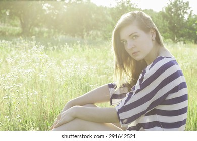 beautiful young woman sitting on hay. The picture shows a sunset