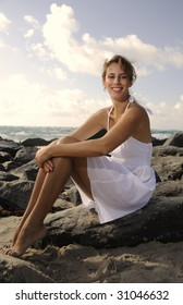 Beautiful young woman sitting on the rocks at the beach