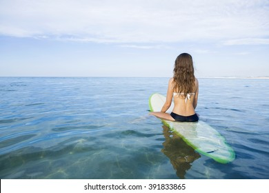 Beautiful young woman sitting on the surfboard and waiting for the waves