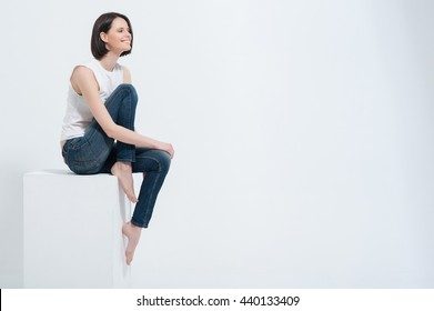 Beautiful young woman sitting on white cube in studio