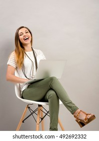 Beautiful young woman sitting on a chair with a laptop and laughing