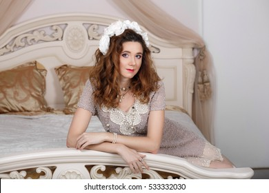 Beautiful young woman sitting on sofa in bedroom.