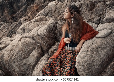 Beautiful young woman sitting on stones outdoors