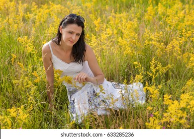 Beautiful young woman sitting on a flowery meadow
