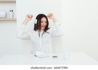 Beautiful young woman sitting on desk and listening to music in white office