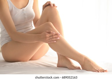 Beautiful young woman sitting on bed at home. Epilation concept