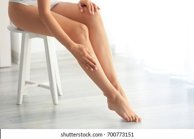 Beautiful young woman sitting on stool at home. Epilation concept