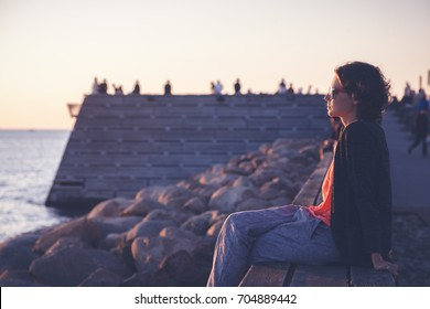 Beautiful young woman sitting on the beach watching the sunset