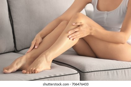 Beautiful young woman sitting on sofa at home. Epilation concept