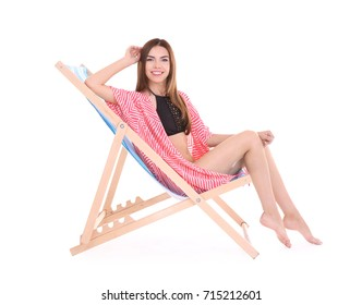 Beautiful young woman sitting on deck chair against white background