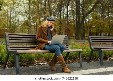 Beautiful young woman is sitting on the bench in the park on an autumn day and she is working on her laptop