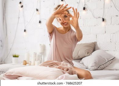 Beautiful young woman sitting on bed and shows gesture heart with fingers. Portrait of smiling lady posing in bright home apartments. Concept happiness and love.