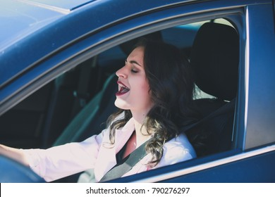 Beautiful young woman sitting on driver seat and singing song out loud while driving.