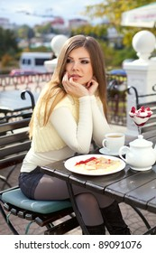 Beautiful young woman sitting in outdoor cafe eating a dessert