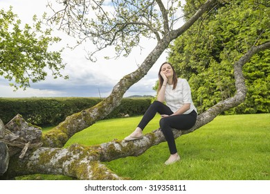A beautiful young woman sitting peacefully on a branch. Outside shot