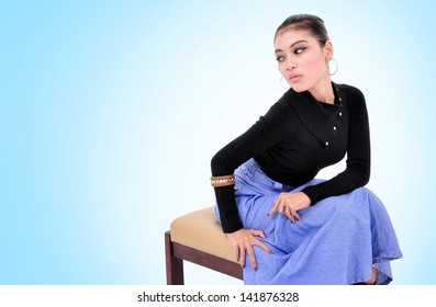 Beautiful young woman sitting with sexy pose, on blue background