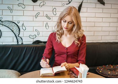 beautiful young woman sitting at a table with a notebook and a phone.