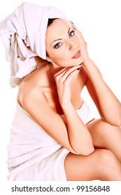 Beautiful young woman sitting in white towel. Spa, healthcare. Isolated over white.