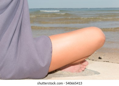 beautiful young woman sitting in yoga pose at the beach