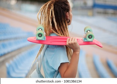 Beautiful young woman with skateboard in the stadium