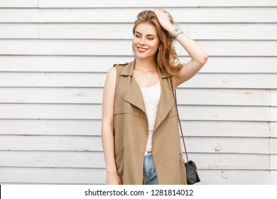 Beautiful young woman of Slavic appearance with a beautiful smile with curly hair in summer fashionable clothes posing near a vintage white wooden wall on a warm summer day. Attractive stylish girl