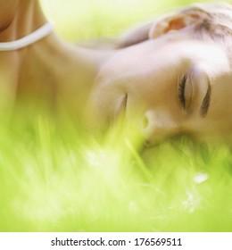 Beautiful young woman sleep on grass