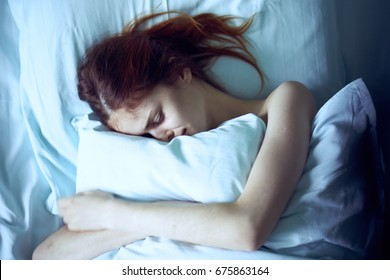 Beautiful young woman sleeping in her bed in the bedroom.
