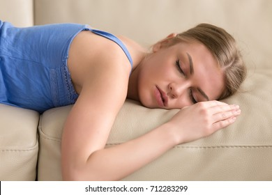 Beautiful young woman sleeping on couch, pretty tired girl lying asleep on sofa, stressed lady taking nap at home passed out after sleepless night, teenager dozing in daytime, head shot portrait