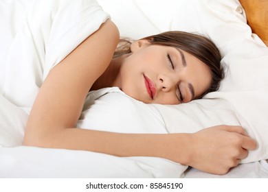 Beautiful young woman sleeping on bed in her bedroom at home